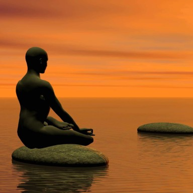 Man meditating on first step on the ocean by beautiful sunset
